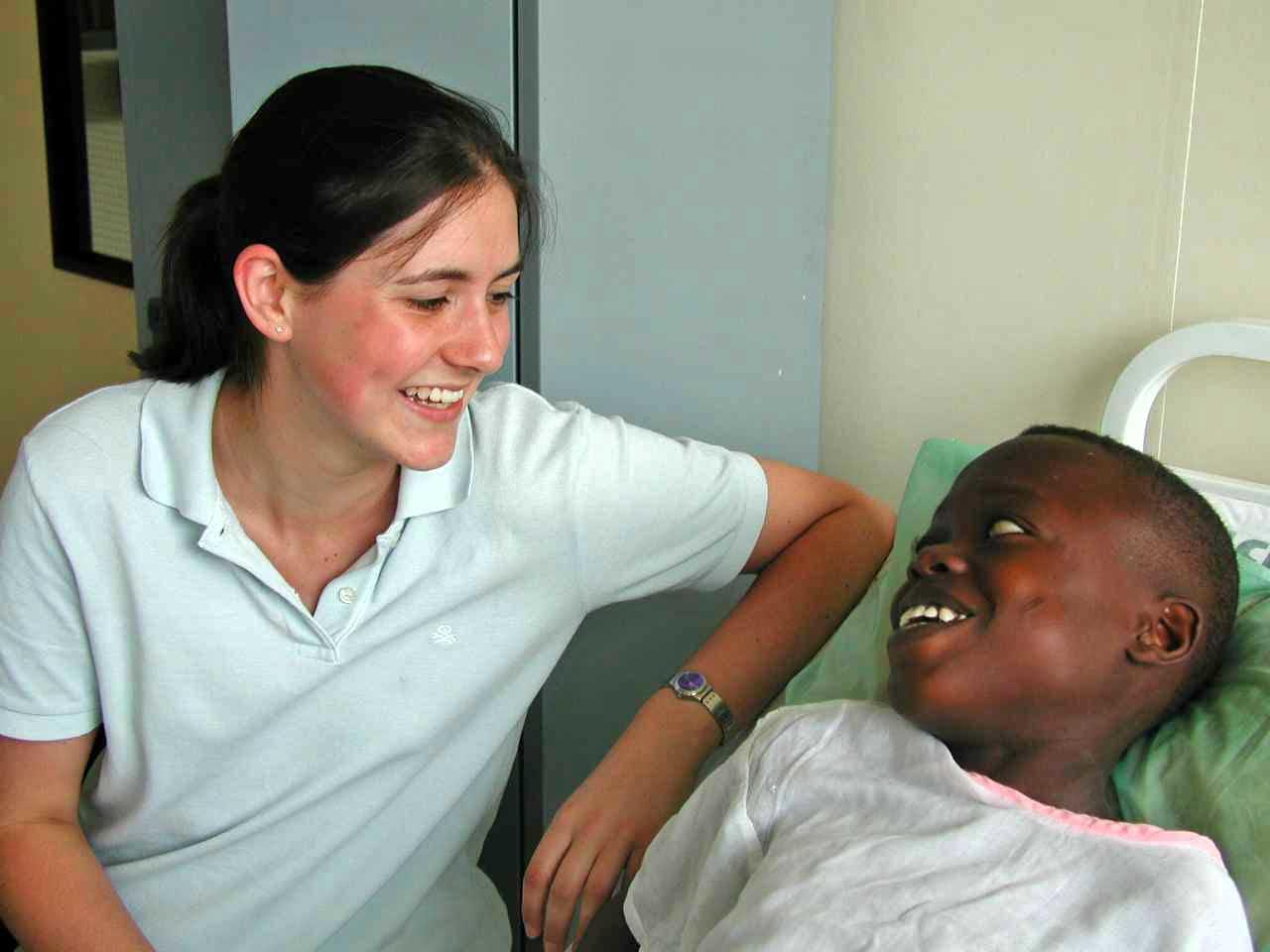 A child and a female healthcare intern are both smiling at each other in a hospital in Ghana,